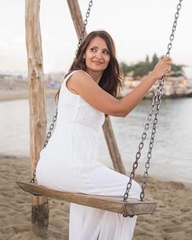 Женщина в полный рост качается на пляже
