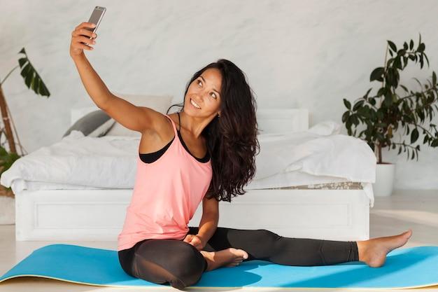 Selfieを取ってフルショットの女性