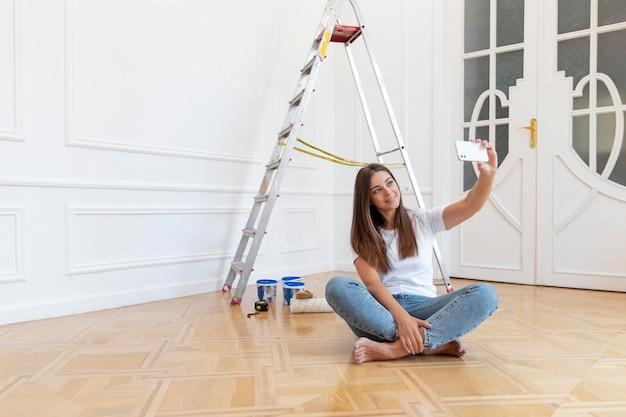 自撮り写真を撮るフルショットの女性