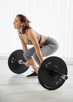 Full shot woman training with dumbbell