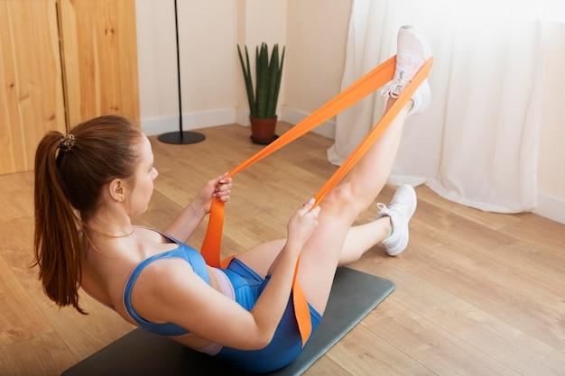 Donna a tutto campo che si allena con l'elastico a casa