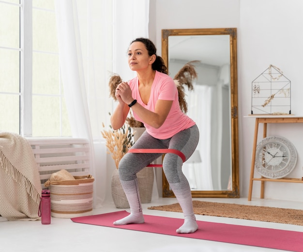 Full shot woman training with resistance band