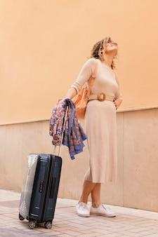 手荷物を持って旅行するフルショットの女性