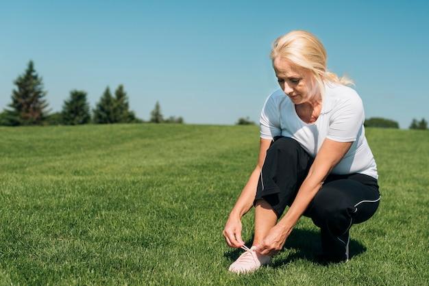 Full shot woman tying her shoe laces