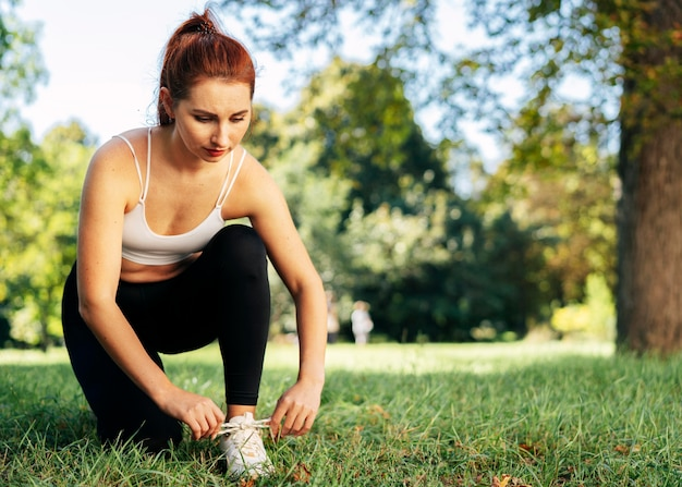 Full shot woman tying her shoelaces outside