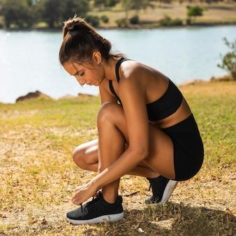 Женщина в полный рост, завязывающая шнурки