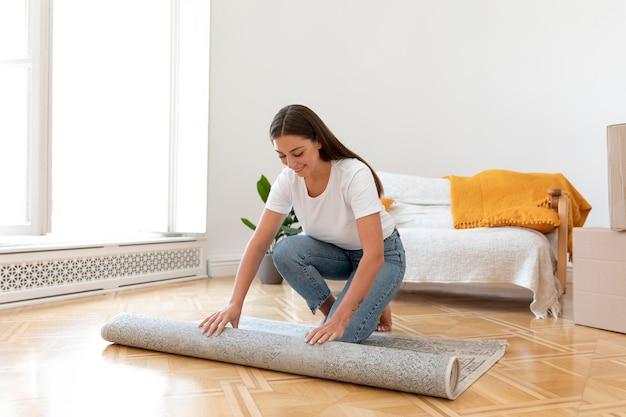 Full shot woman unfolding carpet