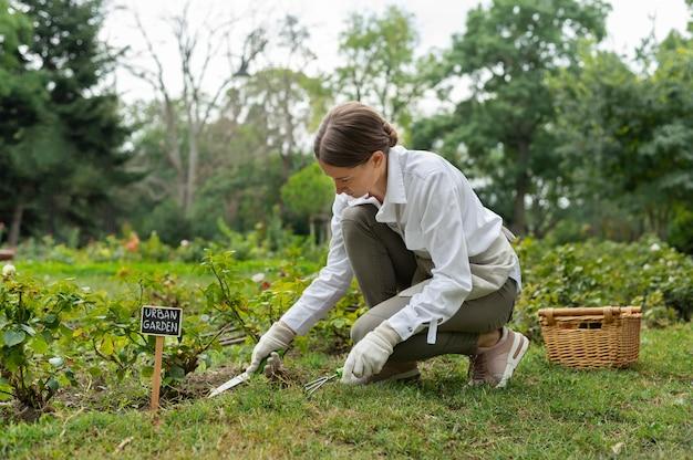 Женщина в полный рост, используя садовые инструменты