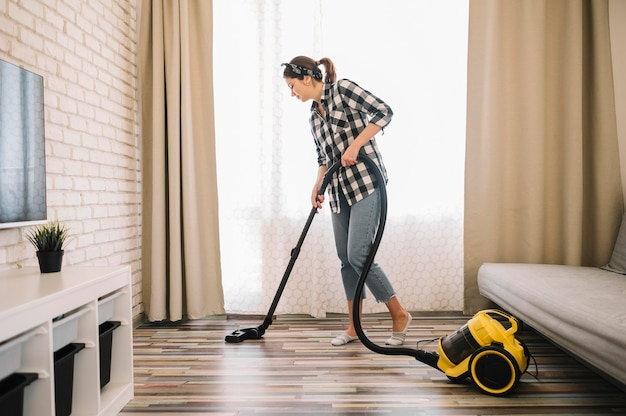 Full shot woman vacuuming in living room