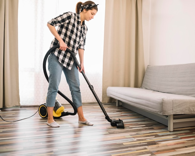 Full shot woman vacuuming