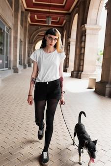 Full shot woman walking dog