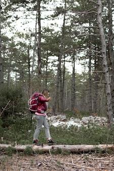 Donna piena del colpo che cammina nella foresta