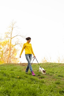 Full shot woman walking her dog in the park