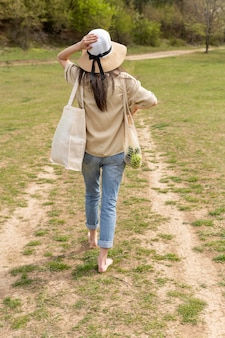 自然の中を歩くフルショットの女性