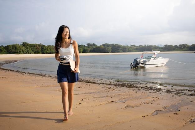 해변에서 걷는 전체 샷 여자
