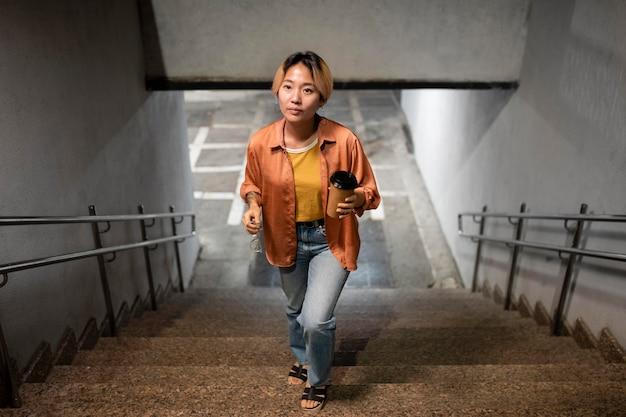 階段を上って歩くフルショットの女性