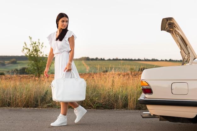 Donna del colpo pieno che cammina con la borsa