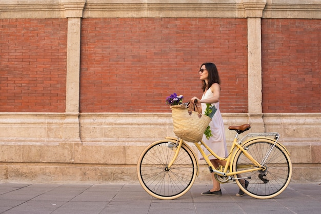 Full shot woman walking with bicycle