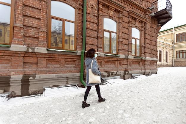 Полный снимок женщины, идущей с маской