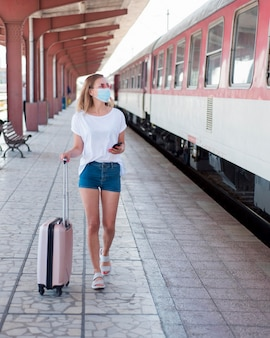 Full shot woman wearing mask with baggage in train station