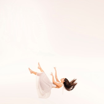Full shot woman in white dress floating