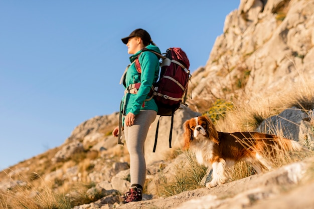 Full shot woman with backpack and dog