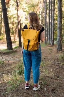 Donna del colpo pieno con lo zaino nella foresta