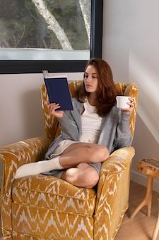 Donna piena del colpo con il libro e la tazza