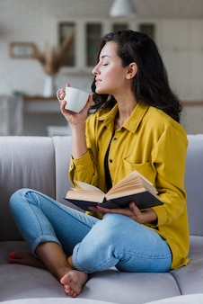 Full shot woman with book enjoying coffee