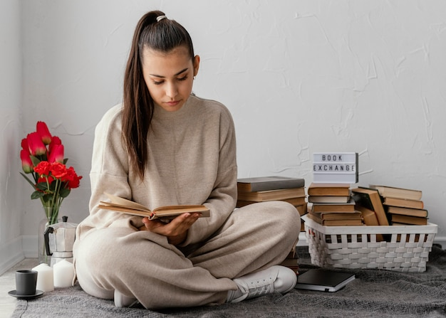 本とチューリップを持つフルショットの女性
