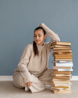 Donna piena del colpo con la pila di libri