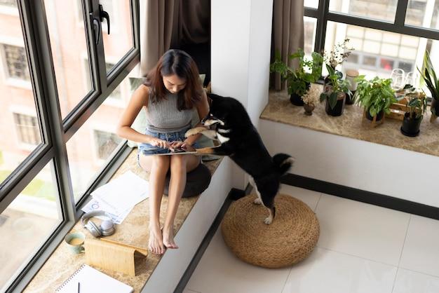 家でかわいい犬とフルショットの女性