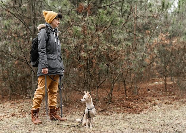 森の中で犬とフルショットの女性