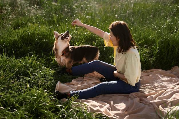 屋外で犬とフルショットの女性