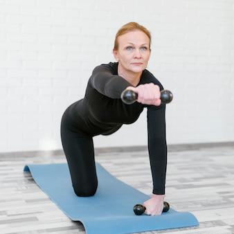 Женщина в полный рост с гантелями на коврике для йоги