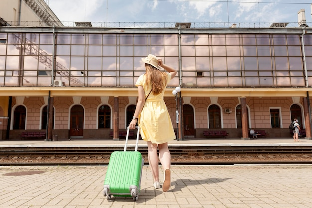 Full shot woman with green luggage