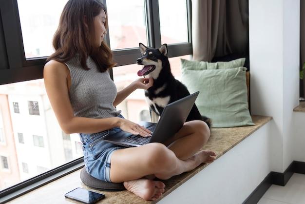 ノートパソコンと犬とフルショットの女性