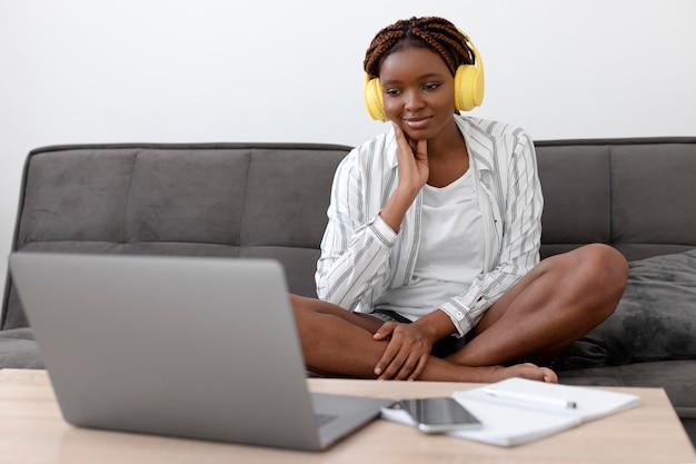 Donna a tutto campo con laptop a casa