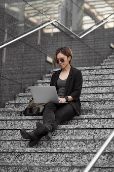 Full shot woman with laptop on stairs