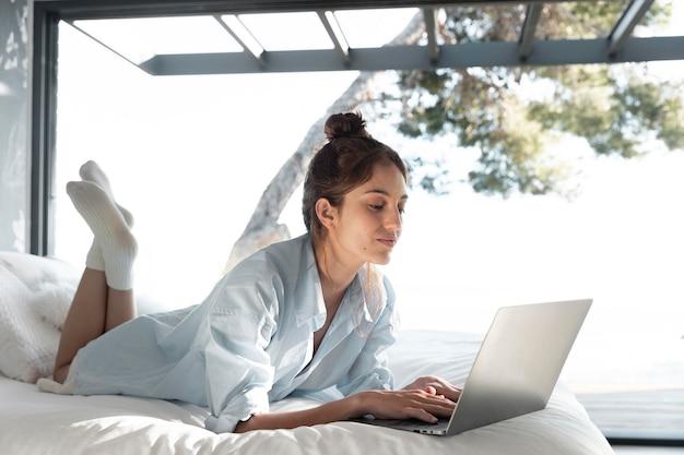 Donna piena del colpo con il computer portatile