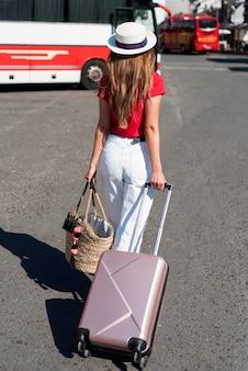 Donna del colpo pieno con i bagagli nella stazione degli autobus