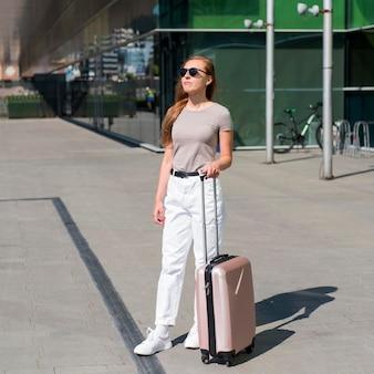 Полный снимок женщины с багажом на станции