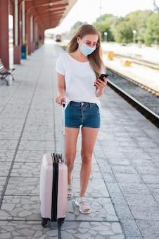 Полный кадр женщина с багажом на вокзале