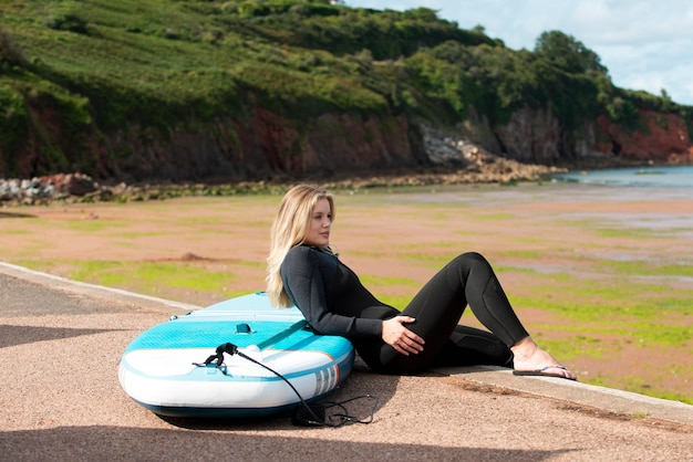 Full shot woman with paddleboard