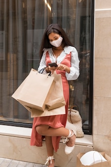 Full shot of woman with shopping bags and smartphone