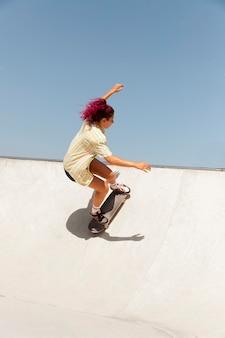 屋外でスケートボードを持つフルショットの女性