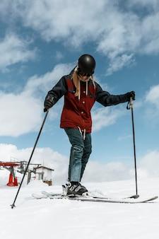 Полный снимок женщины с лыжным снаряжением
