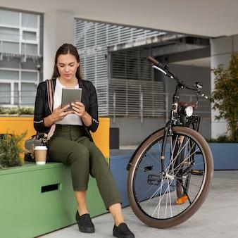 Donna del colpo pieno con tablet e bici
