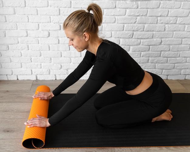 Donna piena del colpo con la stuoia di yoga