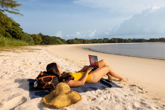 노트북으로 해변에서 일하는 전체 샷 여자